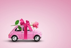 Pink toy car delivering pink rose flower with ribbon and bowon pink background. Valentine day, flowers delivery, women day. Place for text.