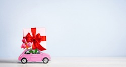 Pink toy retro car with gift box on a roof with bouquet of roses on blue background. Copy space.