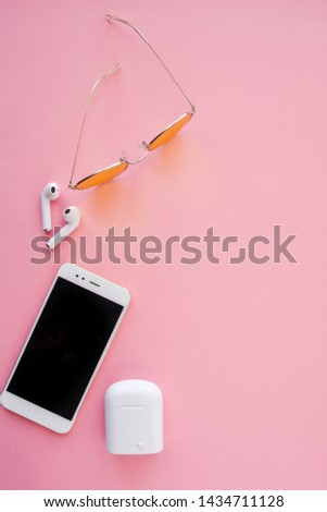 Pink transparent sunglasses, wireless headphones and smartphone are lying on a pink background. Top view. Flatlay. Copyspace center.