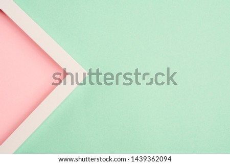 Pink triangle in a frame on a green background. Top view. Copy space