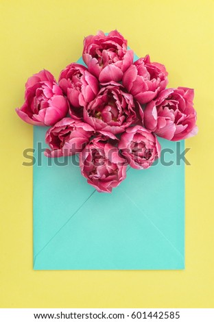 Pink tulip flowers in envelope on yellow background. Floral arrangement #601442585