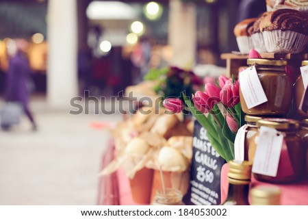 Pink tulips, baked goods, homemade preserves and jams on a farmer\'s market stand