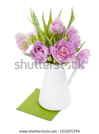 Pink tulips bouquet in pitcher. Isolated on white background