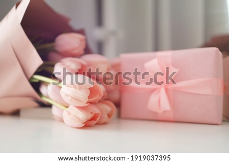Pink tulips flowers and gift or present box pink background. Mothers Day, Birthday, Valentines Day, Womens Day, celebration concept. Space for text.