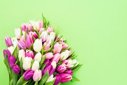 Pink tulips flowers bouquet on a bright green background. Valentine Day, Mothers day, Birthday celebration concept. Top view, copy space for text