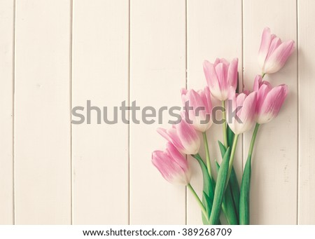 Pink tulips over a white wood table with copy space, in a flat lay composition
