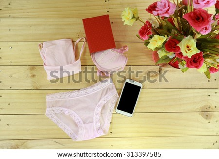 pink underwear and red box with smart phone near roses on wood floor