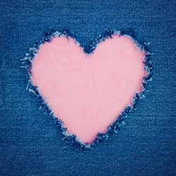 Pink vintage heart shape for copy space torn from blue denim jeans fabric, romantic love concept background