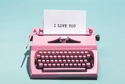 Pink vintage typewriter with a white sheet of paper and