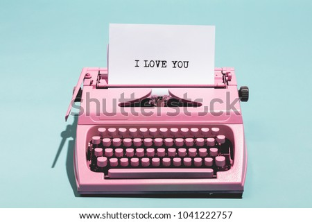 "Pink vintage typewriter with a white sheet of paper and ""I love you"" written on it. Love concept. #1041222757"