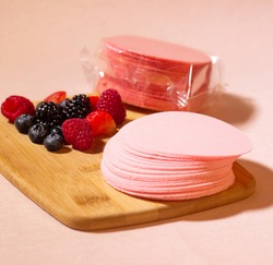 pink wafers laid out on a wooden board and fresh ingredients aside. Red fruits, strawberry, blackberry and blueberry. Selective focus