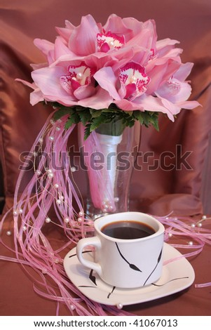 pink wedding bouquet of orchids and a cup of coffee