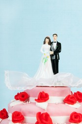 Pink wedding cake with red roses and couple on top on blue background