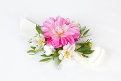 Pink, white and green wrist corsage isolated on white background