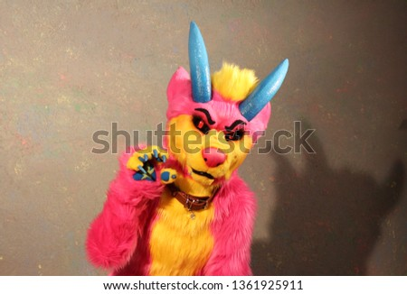 Pink wolf with blue horns and yellow snout and belly raised clawed paw. A soft toy of a large size at a children's party.