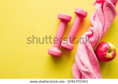 Pink womanly dumbbells, towel and red apple on yellow background. Mock up for women workout plan for summer season. Healthy lifestyle, body slimming concept. Cares about body. Empty place for text.