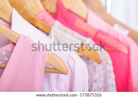 pink womens clothes on hangers on rack in fashion store. closet
