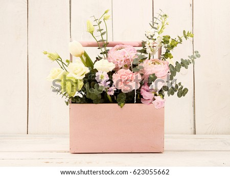 Shutterstock Pink wooden box with flowers roses and carnations in girl's hands on white background