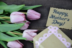 Pink wrapped present with bunch of tulips and mothers day card on wooden table