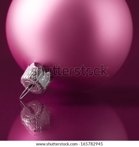 Pink xmas ball on dark purple background - stock photo