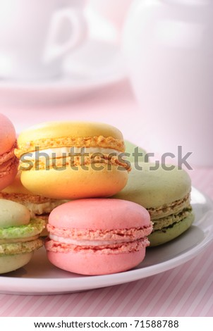 Pink, yellow, green macaroones on white plate close up