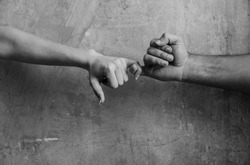 Pinkie promise and friendship. Male and female hands touching each other with little fingers on abstract cement wall on beige background