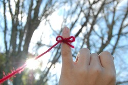 Pinky finger with a red string of destiny in the sky  with the sun