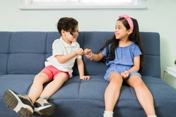 Pinky promise. Cute beautiful girl doing an oath with her little brother. Adorable siblings feeling happy while making a promise