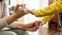 Pinky swear. Close up of mature grandmother and little granddaughter holding pinkie fingers while spending time together at home. Promise, friendship, family concept. Web Banner