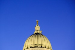 Pinnacle of the capitol building in Madison Wisconsin alight during a clear sunset.