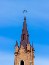 Pinnacle of Transfiguration Church and Organ hall against blue sky in Krasnoyarsk, Russia Catholic church was built in neo-Gothic style in 1908-1911.