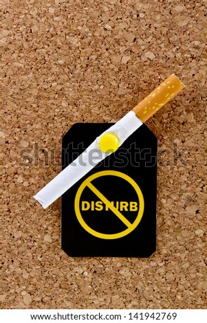Pinned to a cork board filter cigarette with a yellow do not disturb label.Stop smoking concept.