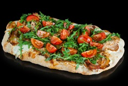 Pinsa romana gourmet italian cuisine on black background. Scrocchiarella traditional dish. Food delivery from pizzeria. Pinsa with meat, arugula, tomatoes, cheese.