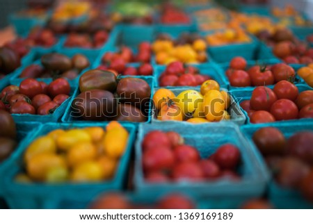 Pint baskets of organic red tomatoes on the counter at a farmer's market. Organic, agriculture products. Freshly, seasonal harvested vegetables. Bio, healthy food. Vegetarian food.