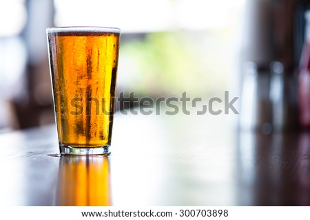 Pint glass of India Pale Ale on long bar in afternoon Stock fotó ©