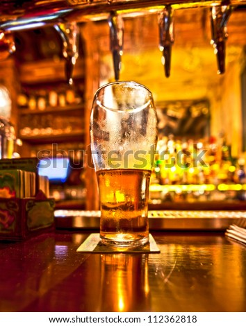 Pint of beer on a bar in a traditional style pub