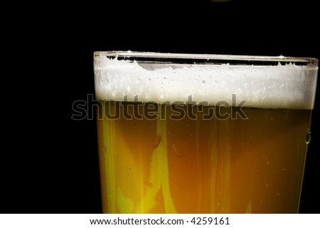 Pint of beer with bubbles, closeup on black - stock photo