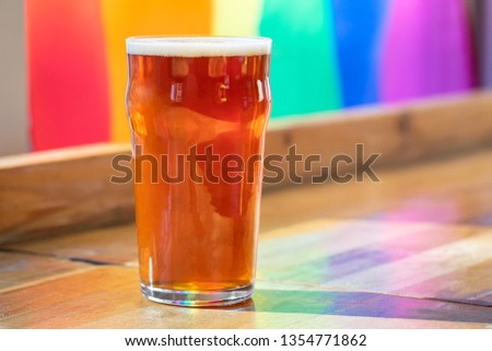 Pint of craft beer in a nonic glass, on a wooden bar with a rainbow flag background, in a LGBTQ happy hour concept, with space for text on the right Stock photo ©