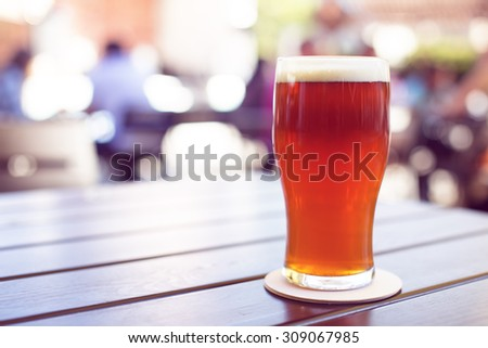 Pint of crafted ale on wooden table in beer garden