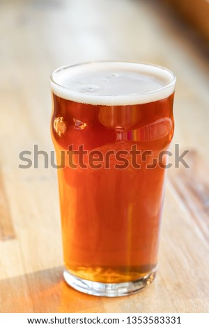 Pint of draft beer in a nonic glass, on a wooden bar at a craft brewery, with space for text on the left Stock photo ©