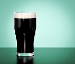 Pint of Irish stout beer on a green background