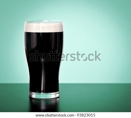 Pint of Irish stout beer on a green background Stock photo ©