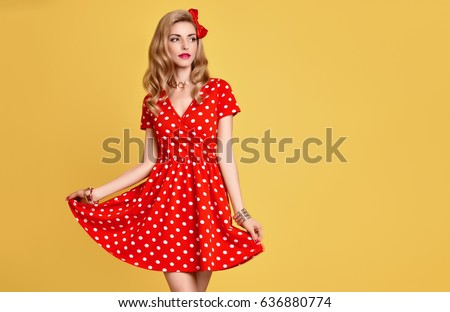 PinUp Beautiful Woman Smiling in Red Polka Dot Fashion Summer Dress. Trendy Stylish Curly hairstyle, Bow. Glamour Blond Having Fun. Pretty Playful Model Girl Happy. Vintage on Yellow #636880774