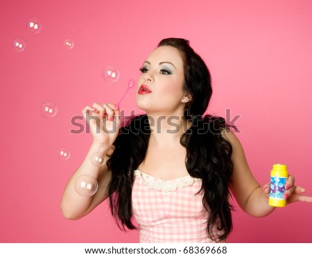 Pinup model blowing soap bubbles - stock photo