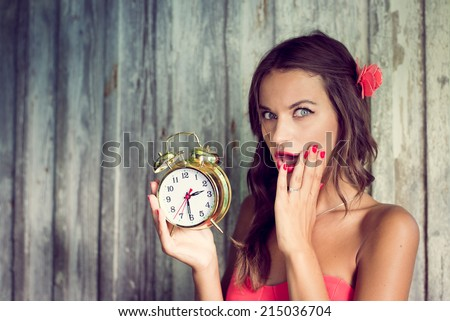 pinup sexy pretty girl surprised looking at camera holding alarm clock in hand on rustic wood copy space background