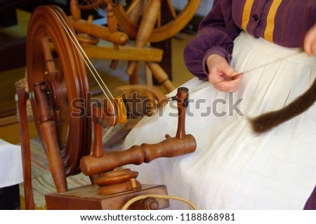 Pioneer lady using Old fashioned wooden spinning wheel