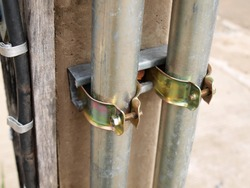 Pipe clamp beams on electric poles. screws and bolts Grips silver metal pipes for fixing electrical conduit. Focus close and choose the subject.