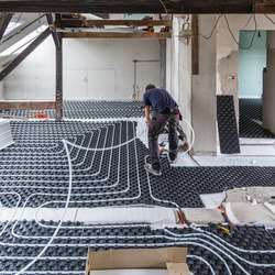 Pipe fitter mounting underfloor heating. Heating system and underfloor heating.