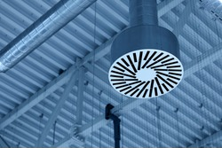 Pipe of the supply and exhaust ventilation system on the ceiling of a commercial room or warehouse.
