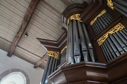 Pipe organ case facade in dark wood with golden decorations in St. Mary's Church of the village Gudow, Schleswig-Holstein, Germany, selected focus, narrow depth of field